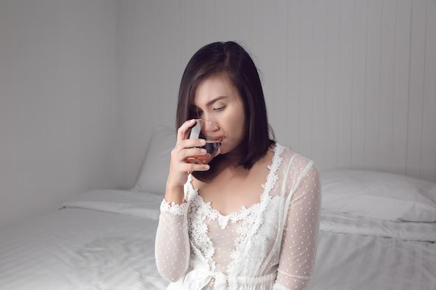 Asiatin im trinkwasser des weißen nachtzugs auf dem bett am schlafzimmer