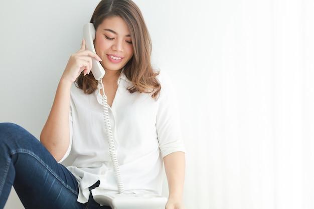 Asiatin im weißen hemd unter verwendung des weinlesetelefons sprechend, im wohnzimmer