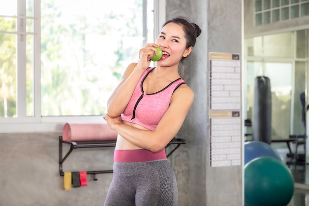 Asiatin in der sportkleidung, die grünen apfel für hält, essen vor training an der eignungsturnhalle