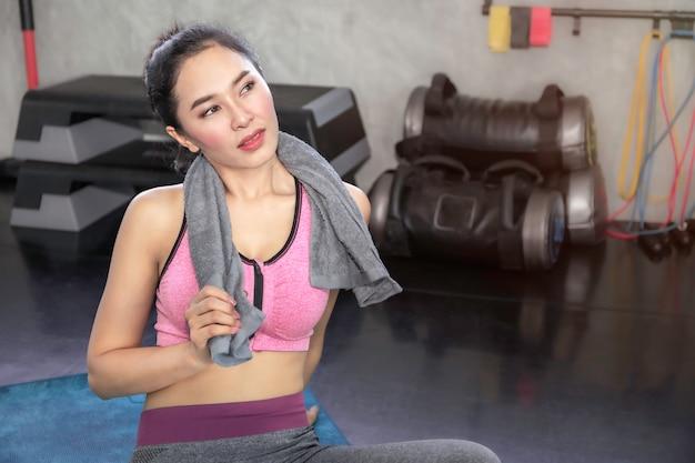 Asiatin in der sportkleidung, die messendes band um ihr wais an der eignungsturnhalle hält