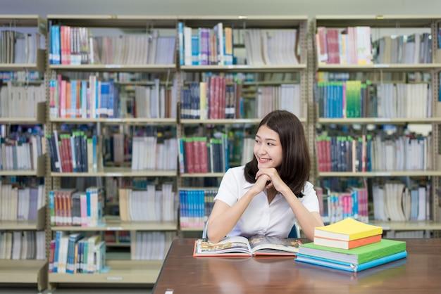 Asiatin in der uniform, die ein buch und ein denken öffnet und liest