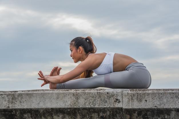 Asiatin in der yogahaltung auf wand.