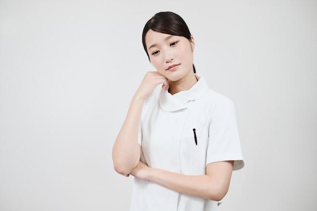Asiatin in einem besorgten weißen kittel