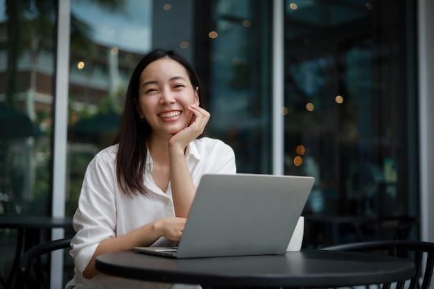 Asiatin in einem café, das an einem laptop arbeitet