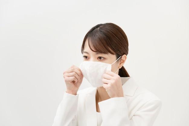 Asiatin in einem weißen anzug, der eine maske und weißen hintergrund trägt