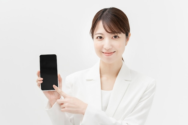 Asiatin in einem weißen anzug mit einem smartphone