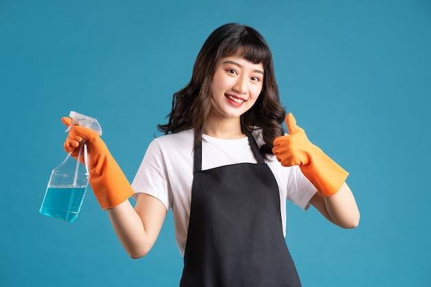 Asiatin in einer schürze und handschuhen, die für den reinigungsjob vorbereiten