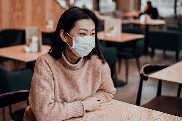 Asiatin in einer schutzmaske sitzt in einem café. schutz der bevölkerung vor viren durch schutz der atemwege. das konzept des coronavirus in der schule