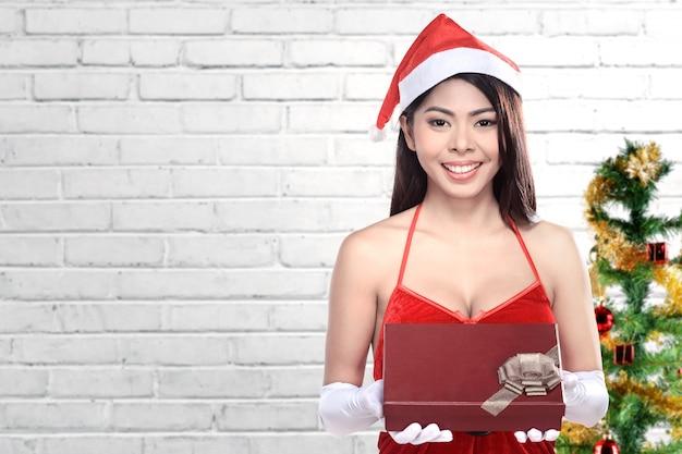 Asiatin in sankt-kostüm, das geschenkbox hält