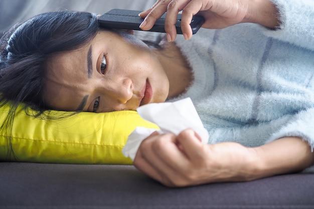 Asiatin ist an erkältung und fieber erkrankt. auf dem sofa im haus liegen, mit dem telefon sprechen und ein trauriges gesicht haben.