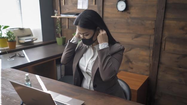 Asiatin korrigiert eine schutzmaske, bevor sie mit einem computer arbeitet. konzept der quarantäne und sozialen distanz