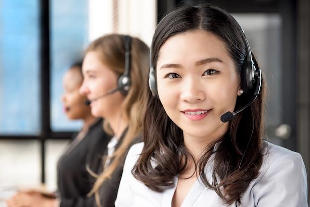 Asiatin-kundendienstvertreter, der in call-center arbeitet