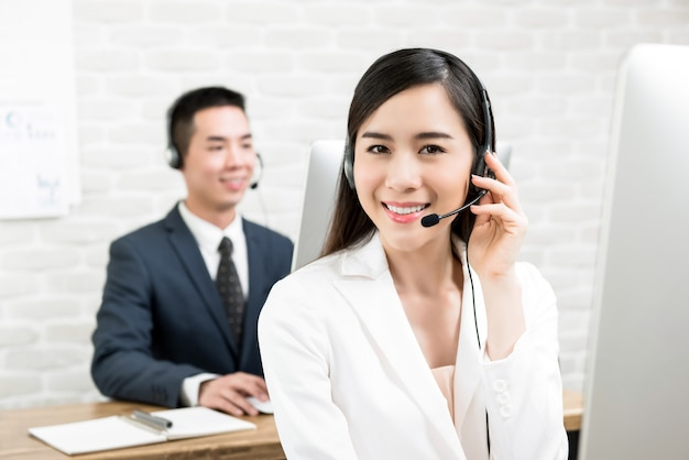 Asiatin-kundendienstvertreter, der in call-center arbeitet