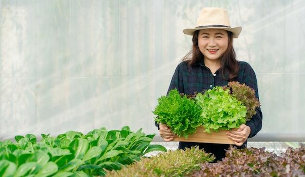 Asiatin-landwirthände, die frisches organisches gemüse in der holzkiste vom hydrokulturbauernhof tragen