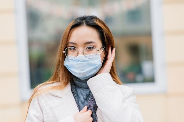 Asiatin mit chirurgischer maske, gesichtsschutz in der stadt, café