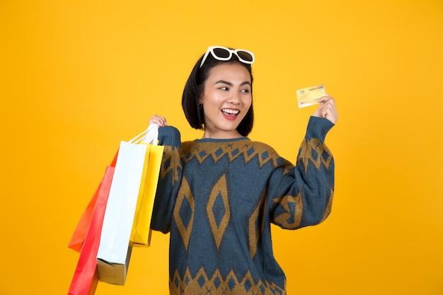 Asiatin mit den gläsern, die bunte papiertüten und eine kreditkarte halten