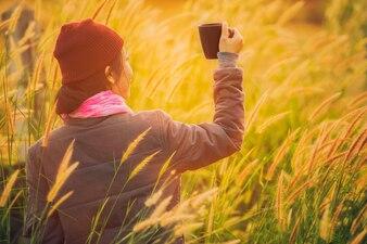 Asiatin mit einem Glas Tee in der Weide.