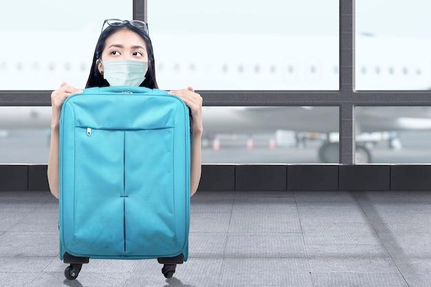 Asiatin mit einer gesichtsmaske mit einem koffer am flughafenterminal. reisen in der neuen normalität