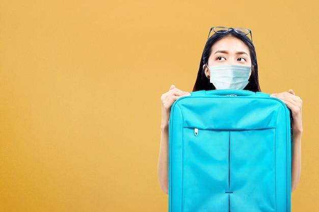Asiatin mit einer gesichtsmaske mit einem koffer. reisen in der neuen normalität