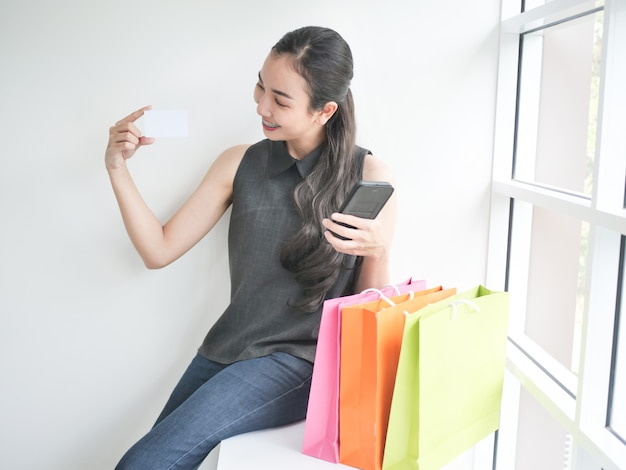 Asiatin mit einkaufstasche im wohnzimmer