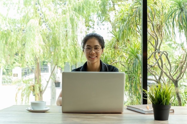 Asiatin mit gläsern auf dem tisch lächelnd unter verwendung des laptops mit tasse kaffee.