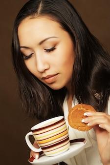 Asiatin mit kaffee und keksen.