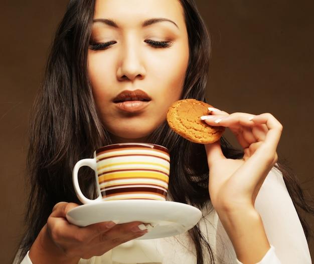 Asiatin mit kaffee und plätzchen.