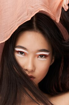 Asiatin mit make-up, rosa stoff, dunkles haar
