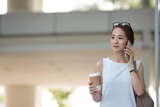 Asiatin mit mitnehmerkaffee gehend in straße und am telefon sprechend