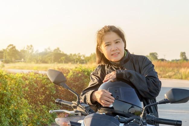 Asiatin mit sturzhelm und tragen und befestigen, bevor sie großes fahrradmotorrad auf die straße zur sicherheit reitet