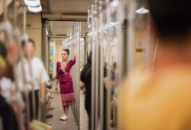 Asiatin mit trachtenkleid im zug, bangkok, thailand, konzeptarbeitsfrau