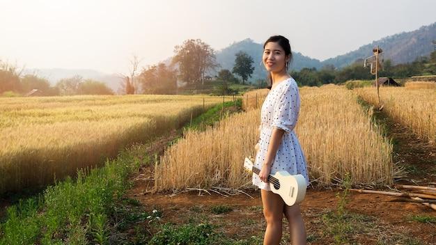 Asiatin mit ukulele im gerstenfeld zur sonnenuntergangzeit