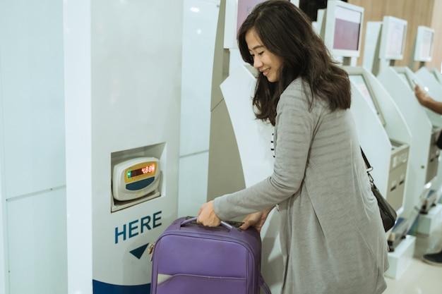 Asiatin nimmt den koffer auf der gepäckwaage