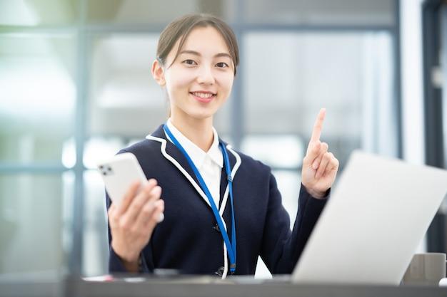 Asiatin posiert mit dem zeigefinger im büro