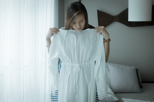 Asiatin probiert zu hause ein neues weißes satingewand an ein mädchen hat gerade eine neue sexy nachtwäsche aus seidenspitze gekauft