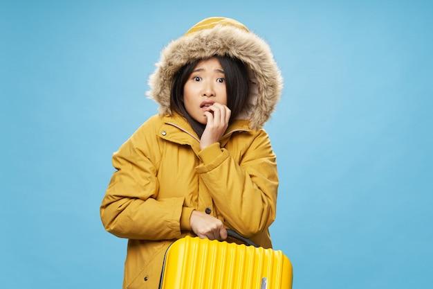 Asiatin reist mit einem koffer in den händen