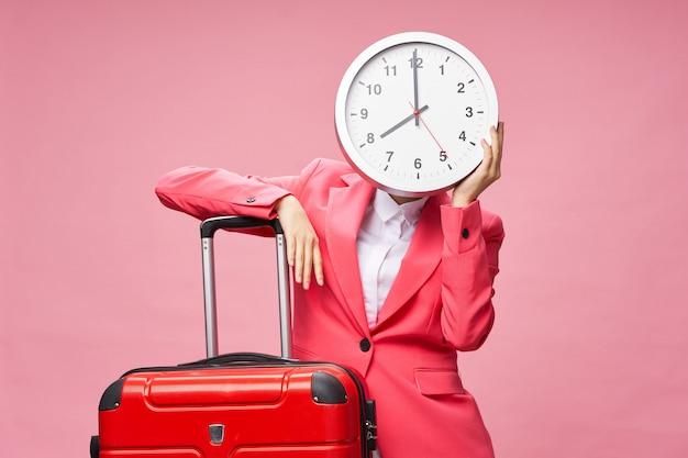 Asiatin reist mit einem koffer und einer großen uhr in den händen, urlaub