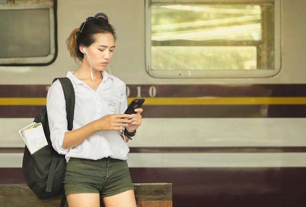 Asiatin-rucksack-reisender. frau, die an der bahnstation steht