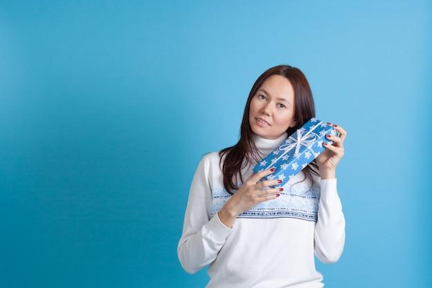 Asiatin schüttelt eine geschenkbox in der nähe ihres kopfes