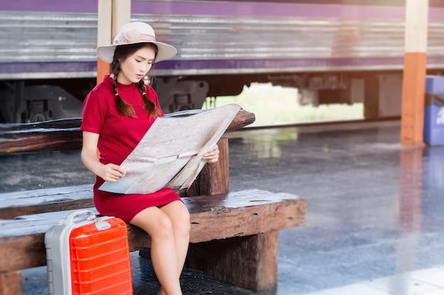 Asiatin schwanger im roten kleid, das rotes gepäck trägt und blick auf die karte an der bahnhofsreise.