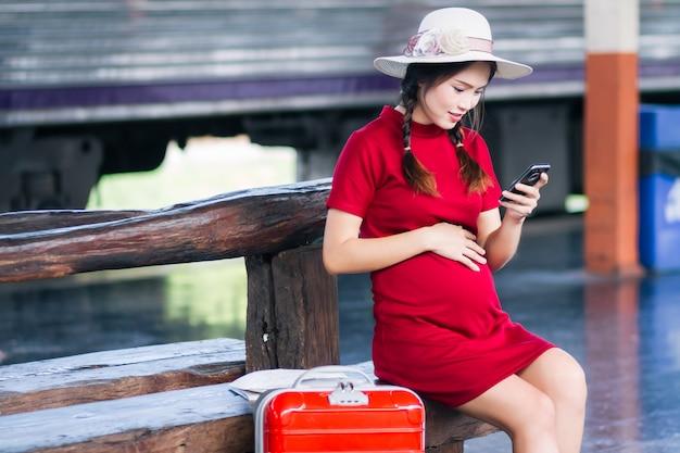 Asiatin schwanger im roten kleid, das rotes gepäck und blick auf das smartphone mit einem roten koffer trägt