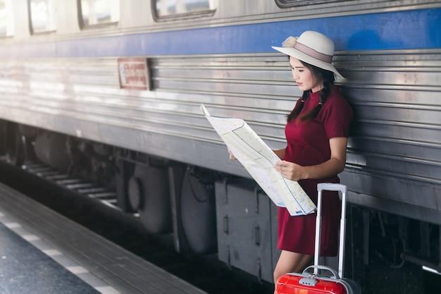 Asiatin schwanger im roten kleid, das rotes gepäck und blick auf die karte auf eisenbahn trägt