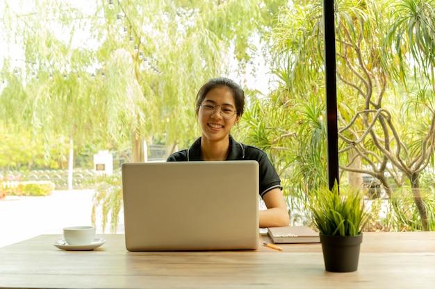 Asiatin setzt den finger, der oben an idee mit laptop in der kaffeestube denkt, an.