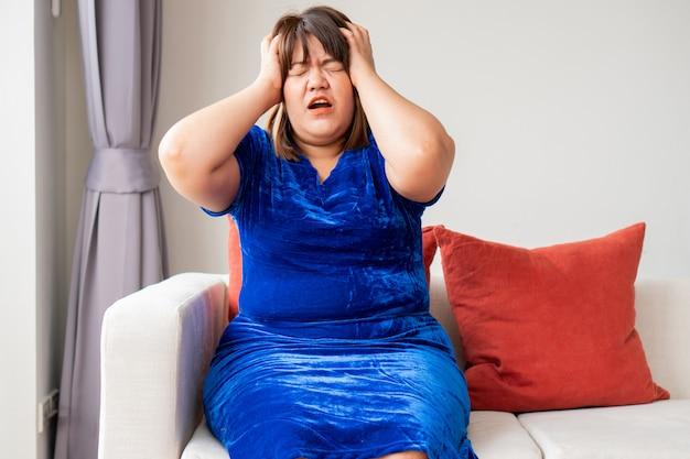 Asiatin sitzt auf dem sofa im wohnzimmer. und händchenhalten im kopf wegen kopfschmerzen