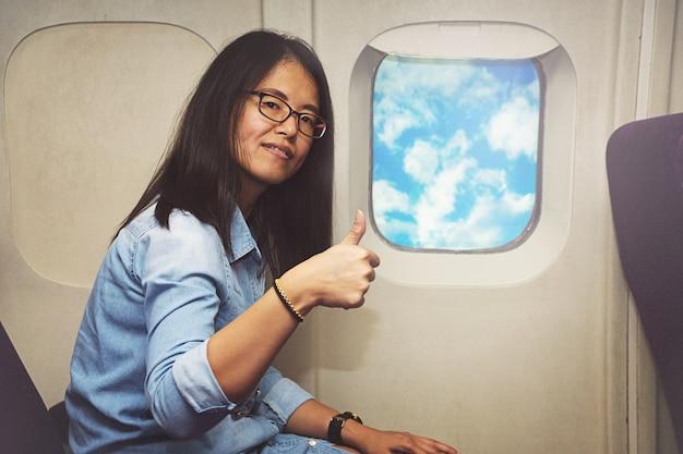 Asiatin sitzt im flugzeug und zeigt sich daumen