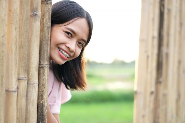 Asiatin steckt ihr gesicht aus einer bambuswand. überraschen