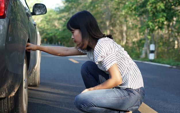 Asiatin suchen sie auf den straßen rund um den wald nach kaputten autos.