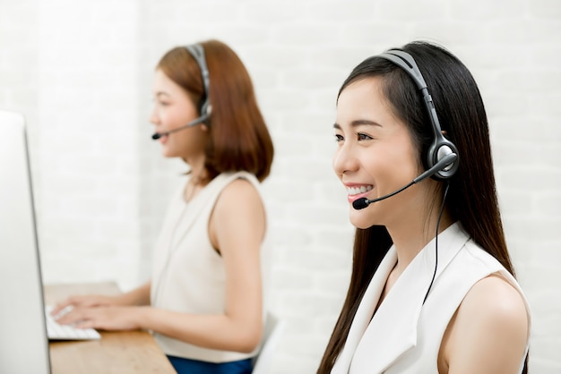 Asiatin-telemarketing-kundendienst-agententeam, das in call-center arbeitet