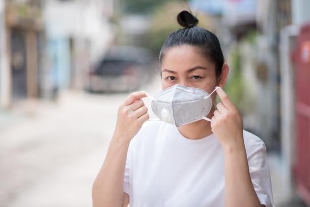 Asiatin trägt eine maske um pm 2,5 staub und koronavirus zu verhindern, covid 19
