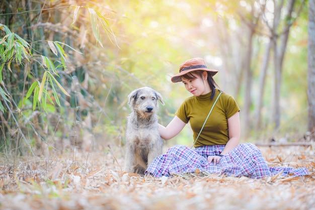 Asiatin und der hund, die im herbstbaumwald am parkhintergrund sitzen - mädchen- und hundemodehaustierkonzept